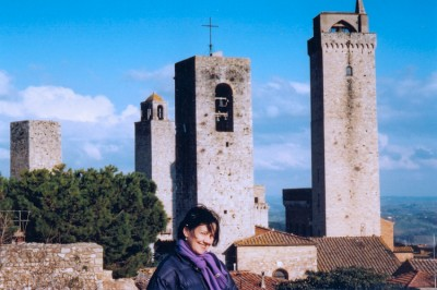 Sonya Conti in front of the city of beautiful towers, San Gimignano. Tuscan Hill Towns tour